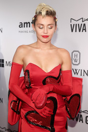 Miley Cyrus teamed red full-sleeve gloves with a heart-embellished gown for a funky-glam look during the amfAR Inspiration Gala.
