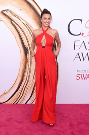 Irina Shayk flashed her cleavage in a red halter jumpsuit by Misha Nonoo while attending the 2016 CFDA Fashion Awards.