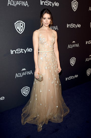Amanda Crew complemented her gown with a geometric gold clutch by Amanda Pearl.