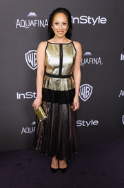 Cheryl Burke added an extra pop of gold with a glitter clutch.