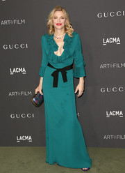 Courtney Love styled her dress with a colorful metallic embroidered clutch.