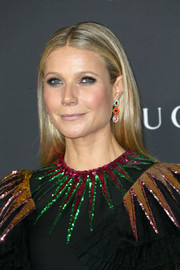 Gwyneth Paltrow dolled up her simple 'do with a colorful pair of dangling gemstone earrings.