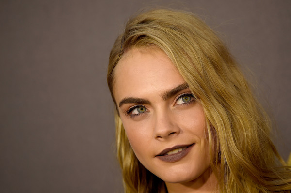 Cara Delevingne went goth with this dark lippy for her MTV Movie Awards beauty look.