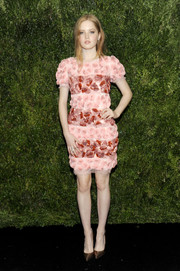 Ellie Bamber went sweet at the MoMA Film Benefit in a sequined and flower-appliqued Chanel dress in various shades of pink and red.