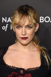 Riley Keough swiped on some deep red lipstick to match the bow on her dress.