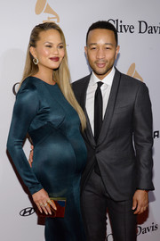 Chrissy Teigen paired a mirrored box clutch by Lee Savage with a slinky teal dress for a modern-glam vibe at the Pre-Grammy Gala.