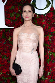 Bebe Neuwirth paired a black frame clutch with a strapless lace gown for a classic look during the 2016 Tony Awards.