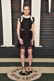 Daisy Ridley looked playfully chic at the Vanity Fair Oscar party in a black Giambattista Valli Couture mini dress with waist cutouts and a flower-adorned neckline.