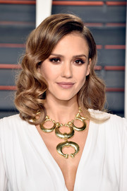 Jessica Alba added an extra dose of glamour with a gold statement necklace by David Webb .