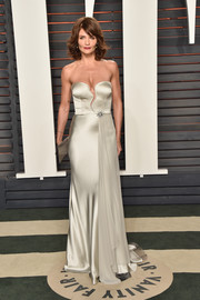 Helena Christensen oozed sex appeal at the Vanity Fair Oscar party in a strapless white satin gown with a slashed bodice.