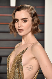For her beauty look, Lily Collins went edgy with smoky eye makeup and dark lipstick.
