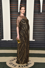 Anne Hathaway complemented her gown with a gold box clutch by Jimmy Choo.