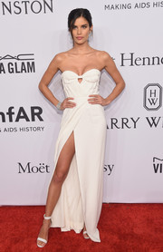 Sara Sampaio flaunted her cleavage and legs at the amfAR New York Gala in a strapless white Burberry gown with a sweetheart neckline and a high slit.