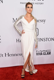 Hailey Baldwin went for futuristic glamour in a white Pamella Roland wrap gown with metallic sleeves at the amfAR Gala.