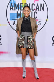 Yara Shahidi mixed and matched a khaki coat with a black button-down and a pair of embellished shorts, all by Prada, for the 2017 American Music Awards.