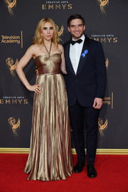 Zosia Mamet caught admiring stares in a gold lame halter gown by Miu Miu at the 2017 Creative Arts Emmy Awards.