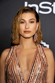 Hailey Baldwin accessorized with a pair of gemstone chandelier earrings for added sparkle to her sequin dress.