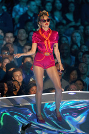 Miley Cyrus matched her blouse with a pair of fuchsia hot pants.