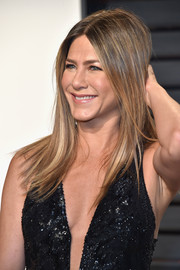 Jennifer Aniston attended the Vanity Fair Oscar party wearing her signature center-parted layers.