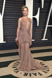 Kate Hudson oozed ultra-feminine appeal at the Vanity Fair Oscar party in a nude Roberto Cavalli lace gown with a plunging neckline and a peplum waist.