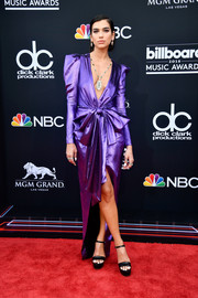 Dua Lipa went for high shine in a metallic purple Alexandre Vauthier gown with a plunging neckline and bow detailing at the 2018 Billboard Music Awards.
