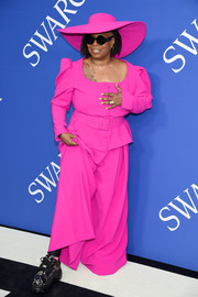 Whoopi Goldberg kept it fun in a bright fuchsia Christian Siriano pantsuit, complete with a matching wide-brimmed hat, at the 2018 CFDA Fashion Awards.
