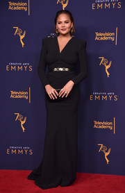 Chrissy Teigen kept it simple in a black Greta Constantine column dress with bold shoulders and a metallic belt at the 2018 Creative Arts Emmy Awards.