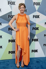 Emily VanCamp charmed in an orange maxi dress with an asymmetrical hem and ruffle detailing at the 2018 Fox Network Upfront.