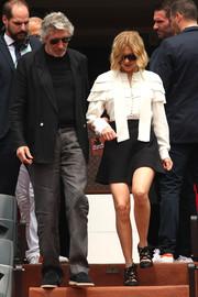 Lea Seydoux paired her top with a flared black mini skirt.