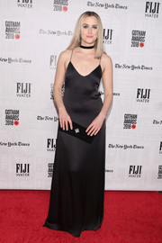 Taylor Schilling complemented her dress with a black velvet clutch.