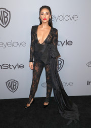 Shay Mitchell looked provocative in a sheer black Dundas jumpsuit with a plunging neckline and an oversized belt at the Warner Bros. and InStyle Golden Globes after-party.