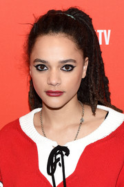Sasha Lane paired her edgy eye makeup with a red lip.