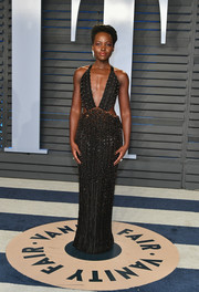 Lupita Nyong'o went majorly vampy in an embellished black Armani Prive gown with waist cutouts and a plunging neckline at the 2018 Vanity Fair Oscar party.
