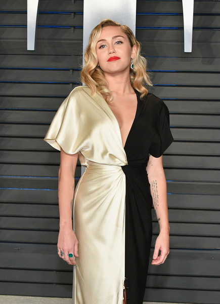 Miley Cyrus paired an Anne Sisteron emerald ring with a two-tone satin gown for total elegance at the 2018 Vanity Fair Oscar party.