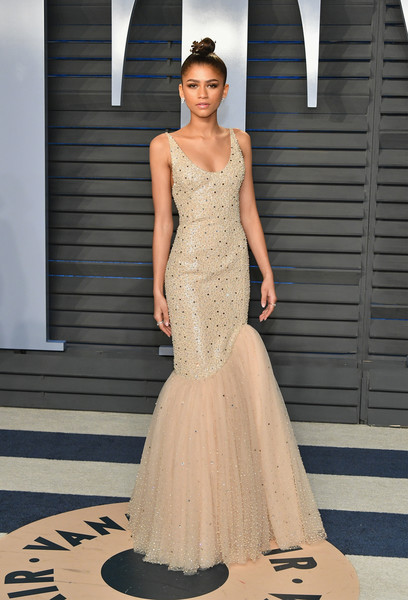Zendaya Coleman looked pageant-ready in an embellished nude mermaid gown by Michael Kors at the 2018 Vanity Fair Oscar party.