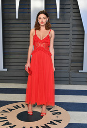 Phoebe Tonkin looked alluring in a red lace slip dress by Christopher Kane at the 2018 Vanity Fair Oscar party.