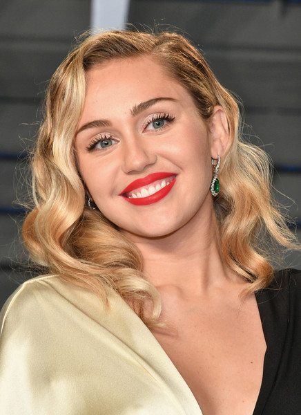 Miley Cyrus wore her tresses down in a tumble of curls at the 2018 Vanity Fair Oscar party.