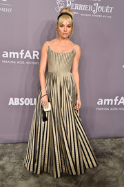 Sienna Miller paired her lovely dress with a tasseled resin purse by The Row.
