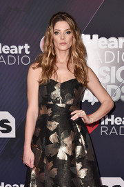Ashley Greene paired a bronze Louise et Cie box clutch with a metallic floral frock for the 2018 iHeartRadio Music Awards.