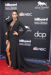 Ciara dropped jaws in a black Stephane Rolland Couture gown with a sheer-panel bodice, sculptural shoulder detail, and a high front slit at the 2019 Billboard Music Awards.