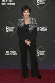 Kris Jenner attended the 2019 E! People's Choice Awards wearing a black Alexander McQueen pantsuit with bejeweled shoulders.