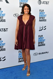 Regina King styled her dress with strappy gold heels by Brian Atwood.