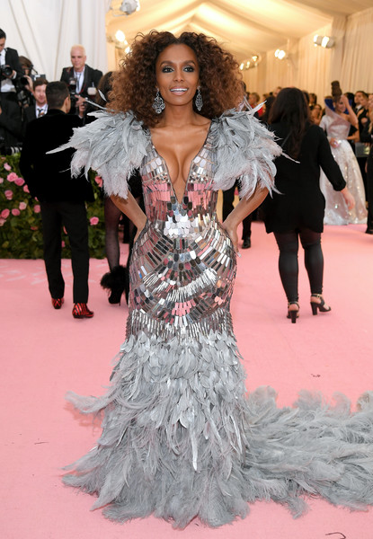 Janet Mock got majorly glam in a feather and paillette mermaid gown by Alberta Ferretti for the 2019 Met Gala.