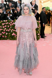 Lucy Boynton looked princessy in a sequined Prada gown with a sheer, feathered overlay at the 2019 Met Gala.