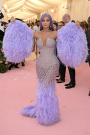 Kylie Jenner showed off her shapely figure in a lilac feathered mermaid gown by Versace at the 2019 Met Gala.