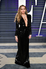 Miley Cyrus oozed sex appeal wearing an Yves Saint Laurent sequined gown with a down-to-the-navel neckline at the 2019 Vanity Fairy Oscar party.