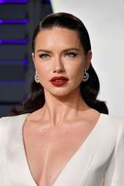 Adriana Lima paired a bold red lip with a cat eye for her beauty look.