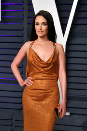 Kacey Musgraves paired a faceted gold clutch by Tyler Ellis with a draped bronze gown for the 2019 Vanity Fair Oscar party.