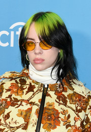 Billie Eilish accessorized with a pair of orange sunnies.