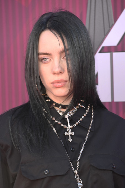 Billie Eilish brightened up her outfit with layers of silver necklaces.